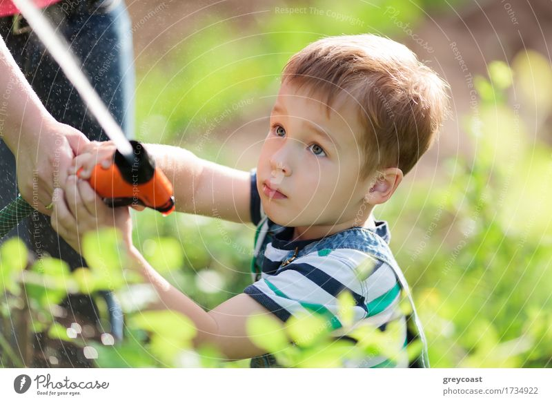 Little boy playing with a jet of water in garden Human being Child Nature Youth (Young adults) Plant Summer Young woman Hand 18 - 30 years Adults Grass