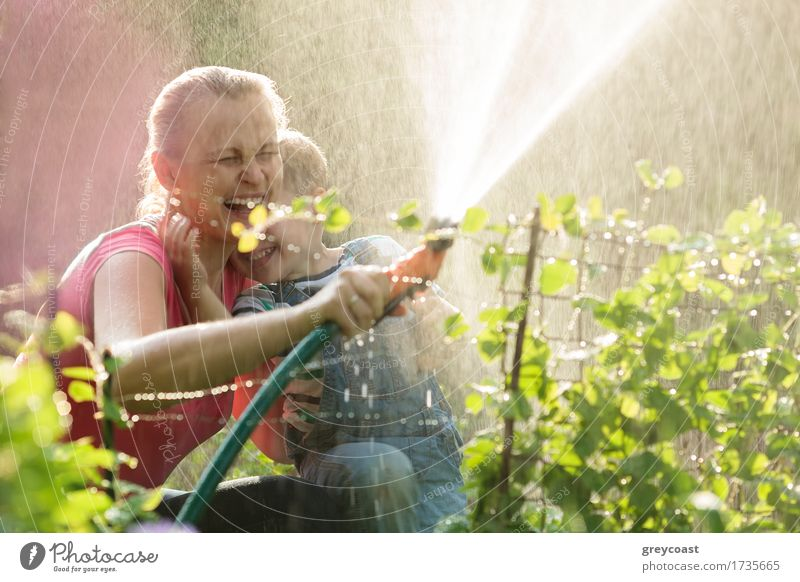 Laughing mother and son playing with a sprinkler Joy Happy Playing Summer Garden Child Boy (child) Mother Adults Family & Relations Nature Plant Grass Bushes