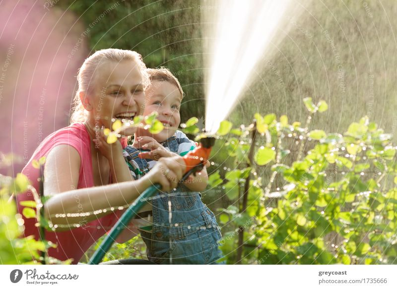 Mother and son playing with water Joy Happy Playing Summer Garden Child Boy (child) Adults Family & Relations 2 Human being Nature Plant Grass Bushes Laughter