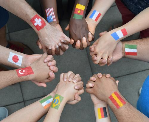 Nations hand in hand - people of different nationalities with painted flags holding hands as a sign of peace and solidarity Human being by hand Group Sign Flag
