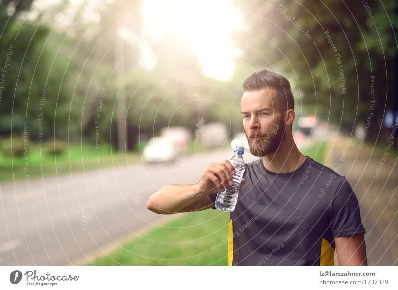Young bearded man drinking bottled water Drinking Lifestyle Face Summer Man Adults 1 Human being 18 - 30 years Youth (Young adults) Warmth Beard Fitness