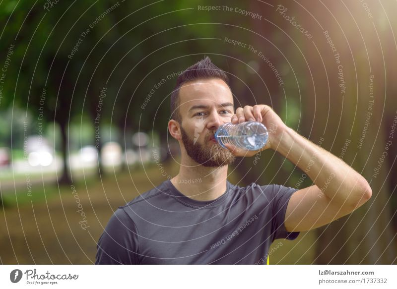 Young man drinking bottled water Drinking Lifestyle Face Summer Masculine Man Adults 1 Human being 18 - 30 years Youth (Young adults) Warmth Beard Fitness