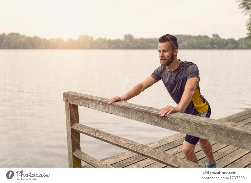Young man doing stretching exercises Human being Youth (Young adults) Man Summer 18 - 30 years Face Adults Warmth Sports Lifestyle Wood Lake Masculine