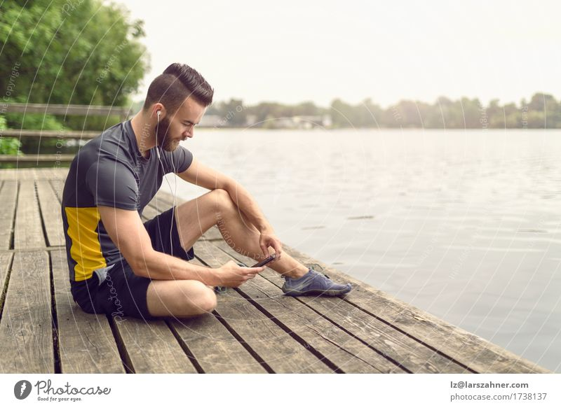 Attractive bearded young man relaxing on a wooden deck Lifestyle Face Relaxation Music PDA Masculine Man Adults 1 Human being 18 - 30 years Youth (Young adults)
