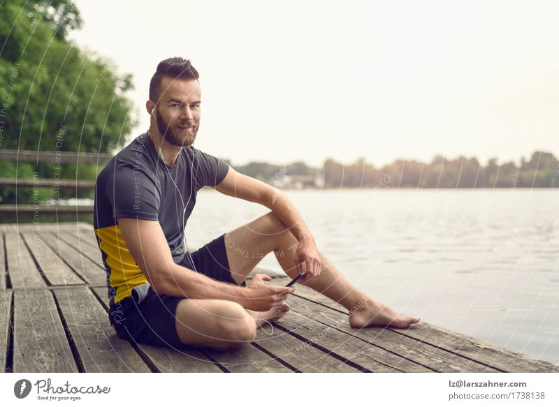 Attractive bearded young man relaxing on a wooden deck Lifestyle Face Relaxation Music Telephone PDA Man Adults 1 Human being 18 - 30 years Youth (Young adults)