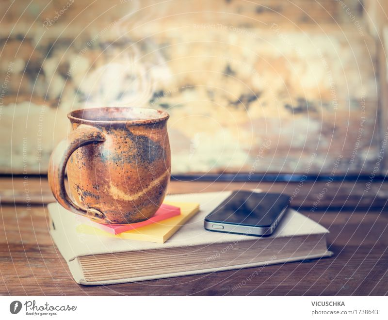 Cup with hot drink on book with smart phone Beverage Hot drink Coffee Tea Lifestyle Style Design Living or residing Table Cellphone PDA Retro Vintage Steam Book