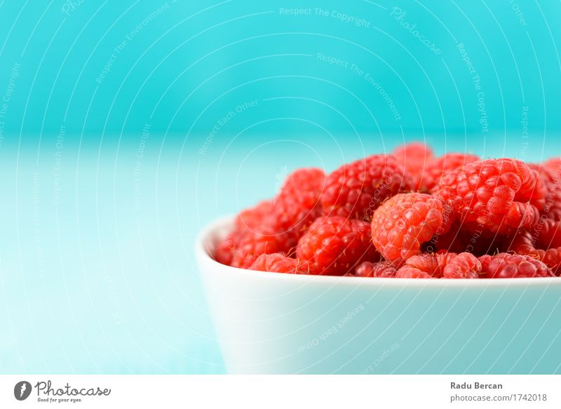 Red Raspberries In Bowl On Turquoise Background Blue Colour White Eating Healthy Food Fruit Copy Space Nutrition Sweet Simple Clean Organic produce Breakfast