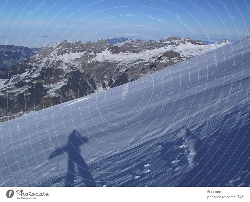 boarder Snowboard Alps Mountain Snowcapped peak Shadow Snow layer Carrying Upward Snowboarder Winter vacation Slope Panorama (View) Beautiful weather