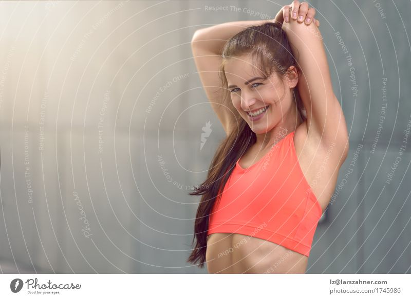 Fit athletic young woman doing stretching exercises Human being Woman Youth (Young adults) Girl 18 - 30 years Face Adults Sports Lifestyle Happy Gray Copy Space Body Action Arm Smiling