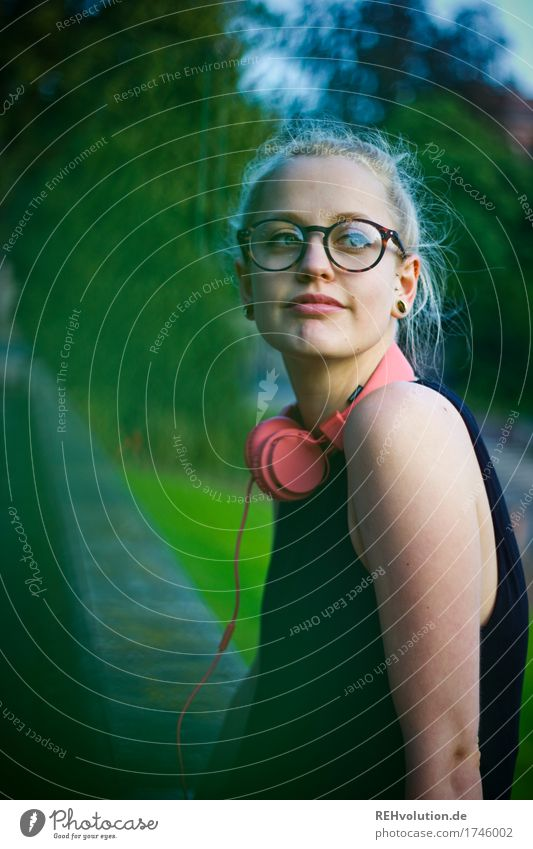 A young woman leans against a wall Upper body portrait Central perspective Shallow depth of field blurriness Day Exterior shot Colour photo Hipster Future