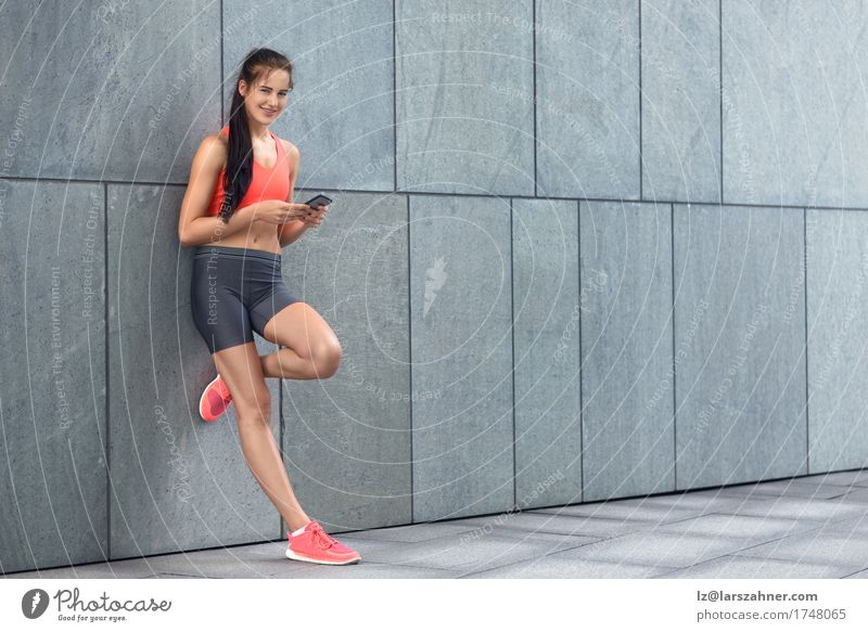 Sporty young woman checking her mobile Human being Woman Youth (Young adults) Summer 18 - 30 years Face Adults Warmth Copy Space Modern Stand Smiling Fitness Telephone Athletic Brunette