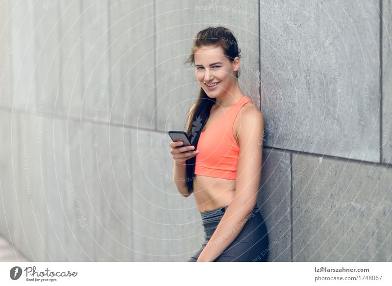 Sporty young woman with her mobile Human being Woman Youth (Young adults) Summer 18 - 30 years Face Adults Warmth Copy Space Modern Stand Smiling Fitness Telephone Athletic Brunette