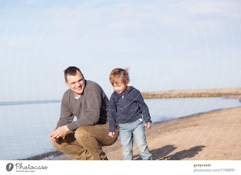 Smiling father with his young son at the beach crouching down on the sand with a smile as the boy stands alongside him Joy Happy Beach Ocean Boy (child) Father