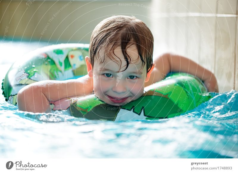 Young boy in inflatable tube swimming Joy Happy Relaxation Spa Swimming pool Child Boy (child) 3 - 8 years Infancy Water Ring To enjoy Smiling Laughter Small