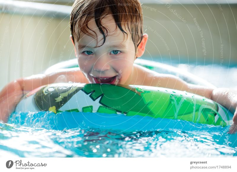 Boy in inflatable ring having fun Human being Child Water Relaxation Joy Boy (child) Laughter Small Happy Action To enjoy Smiling Swimming pool Ring Horizontal