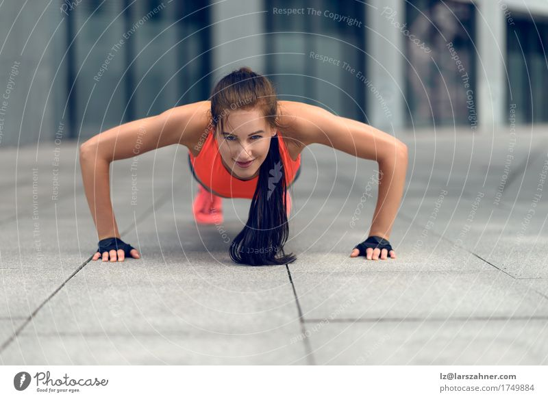 Fit young woman doing push-ups Human being Woman Youth (Young adults) Summer 18 - 30 years Face Adults Sports Lifestyle Copy Space Fitness Thin Brunette Town Conceptual design Practice