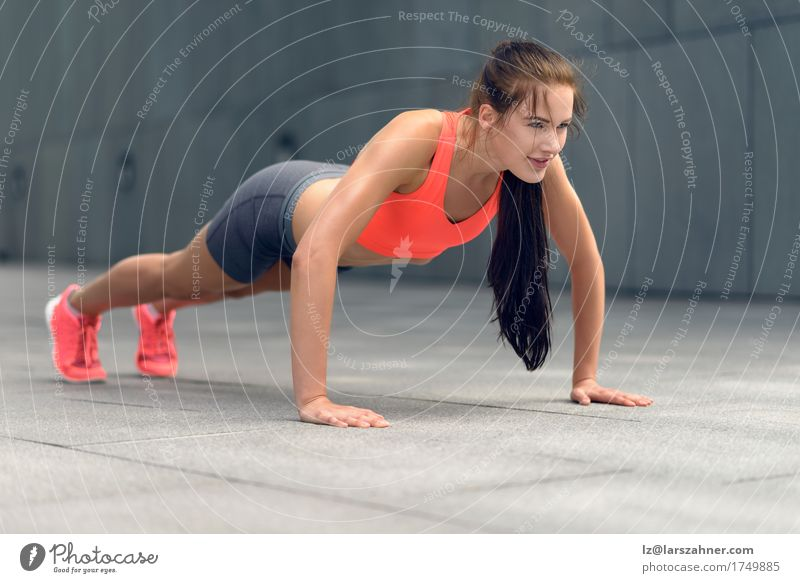 Fit young woman doing push-ups Human being Woman Youth (Young adults) Summer 18 - 30 years Adults Sports Lifestyle Copy Space Fitness Thin Brunette Town Conceptual design Practice