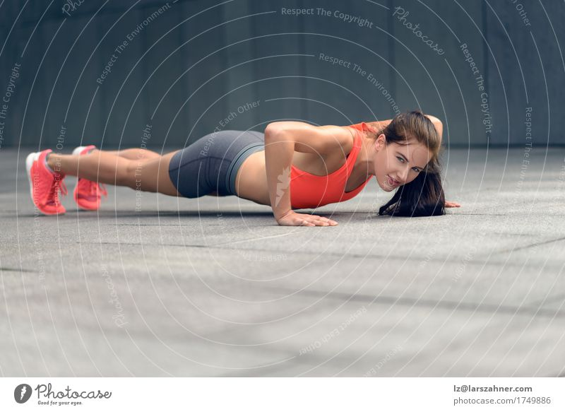 Fit young woman doing push-ups Human being Woman Youth (Young adults) Summer 18 - 30 years Face Adults Sports Lifestyle Copy Space Fitness Thin Brunette Town