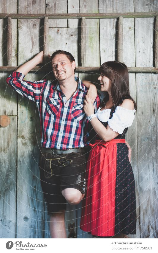 Young couple in traditional costume in front of a wooden hut Lifestyle Tourism House (Residential Structure) Oktoberfest Fairs & Carnivals Human being Masculine