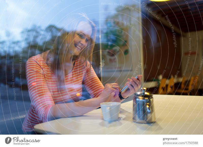 View through the glass window of a young woman using a mobile phone in a cafeteria smiling as she reads a text message Hot drink Coffee Tea Happy Restaurant