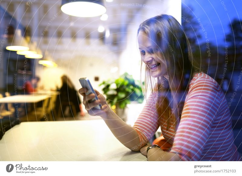 View through the plate glass window with reflections of a young woman sitting in a restaurant using a mobile reading a text message with a smile Happy