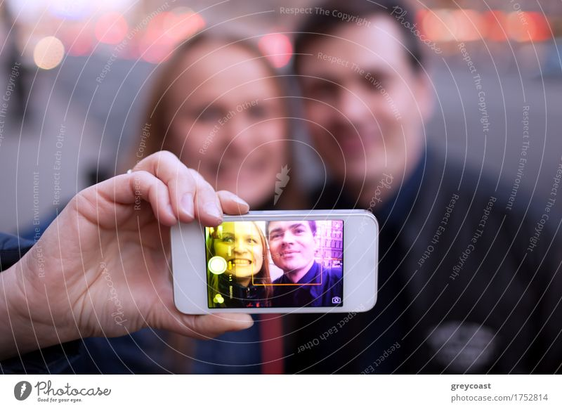 Happy couple taking self portrait Joy Face Telephone PDA Human being Young woman Youth (Young adults) Young man Friendship Couple 2 18 - 30 years Adults Town