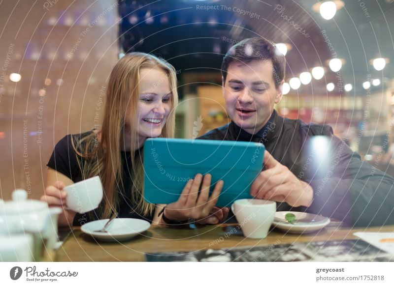 Young people drinking coffee and looking on pad Human being Youth (Young adults) Young woman Young man 18 - 30 years Adults Laughter Happy Couple Blonde Smiling Computer Coffee Restaurant Café Meeting