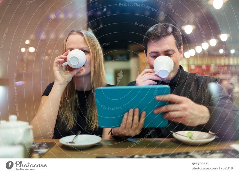Man and woman drinking coffee while holding a smart tablet Coffee Tea Restaurant Meeting Computer Young woman Youth (Young adults) Young man Couple 2