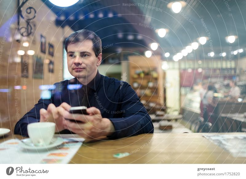 Man at the table texting and drinking a cup of coffee in the cafe Coffee Restaurant Telephone PDA Homosexual Young man Youth (Young adults) 1 Human being
