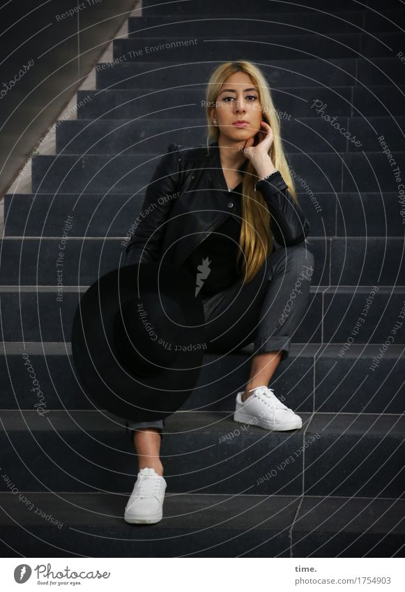 . Feminine 1 Human being Wall (barrier) Wall (building) Stairs Pants Jacket Sneakers Hat Blonde Long-haired Observe Think To hold on Looking Sit Wait Beautiful