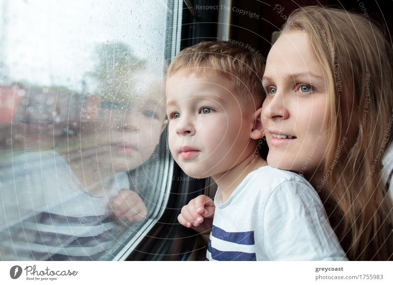 Mother and son looking through a train window as they enjoy a days travel with the small boys face reflected in the glass Vacation & Travel Trip Child