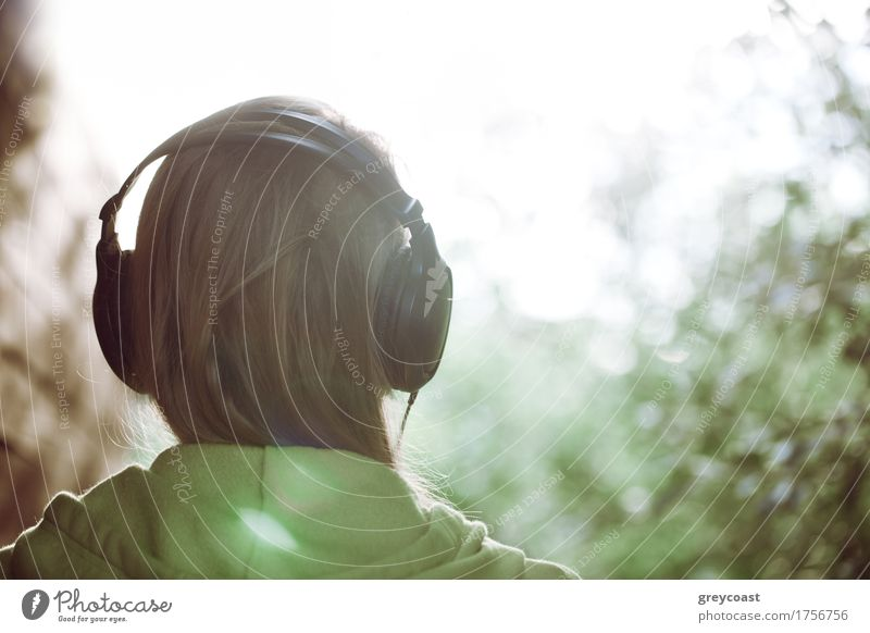 Woman in headphones against bright sunlight Human being Nature Youth (Young adults) Colour Green Young woman Sun Tree Landscape Relaxation Style Garden Bright