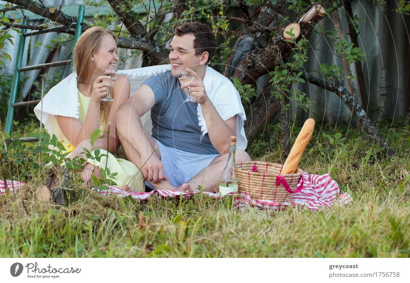 Happy young couple on picnic in the country. They sitting on the grass with glasses of wine covered with blanket. Romantic moments together Beverage