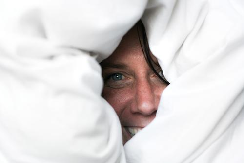 Female face looks laughing from the duvet Lifestyle Joy Leisure and hobbies Woman Adults Face 1 Human being 30 - 45 years Duvet Bedclothes smile Laughter