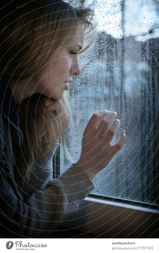 woman looking through window with raindrops Human being Woman Youth (Young adults) Blue Young woman Loneliness Winter Window 18 - 30 years Adults Sadness