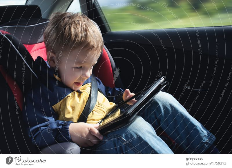 Excited little boy in the car playing with touchpad sitting in child safety seat Joy Happy Playing Vacation & Travel Trip Child Computer Boy (child) 1