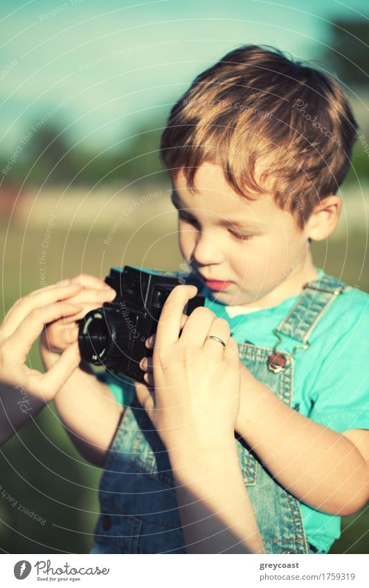 Mother helping her little son to take his first pictures outdoor. Focus on mothers hands. Instagram style color toned Summer Child Camera Boy (child) Adults