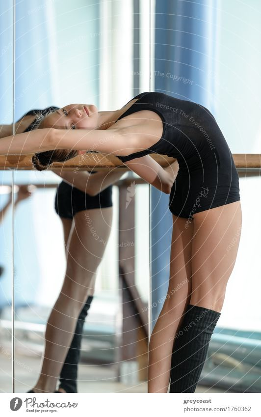 Young ballet dancer stretching out at the barre Human being Youth (Young adults) Girl School 13 - 18 years Dance Academic studies Fitness Railroad Thin Mirror