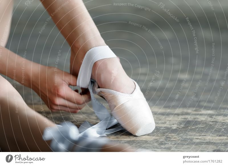 Close-up shot of a ballerina taking off the ballet shoes sitting on the floor in the studio Elegant Beautiful Academic studies Dancing school Girl