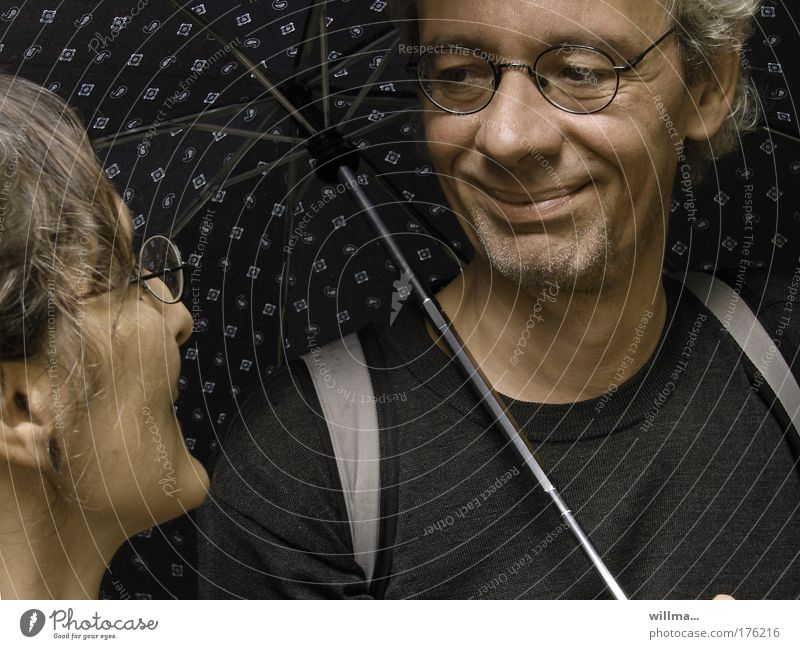 Couple with umbrella he smiles at her Flirt Woman Man Umbrella Friendship Partner Eyeglasses Emotions Moody Contentment Trust Safety (feeling of)