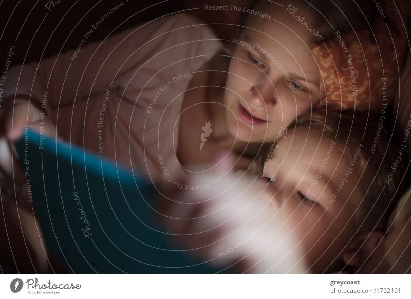Mother and little son watching video or playing on touchpad lying in bed at night Playing Child Computer Boy (child) Young woman Youth (Young adults) Adults