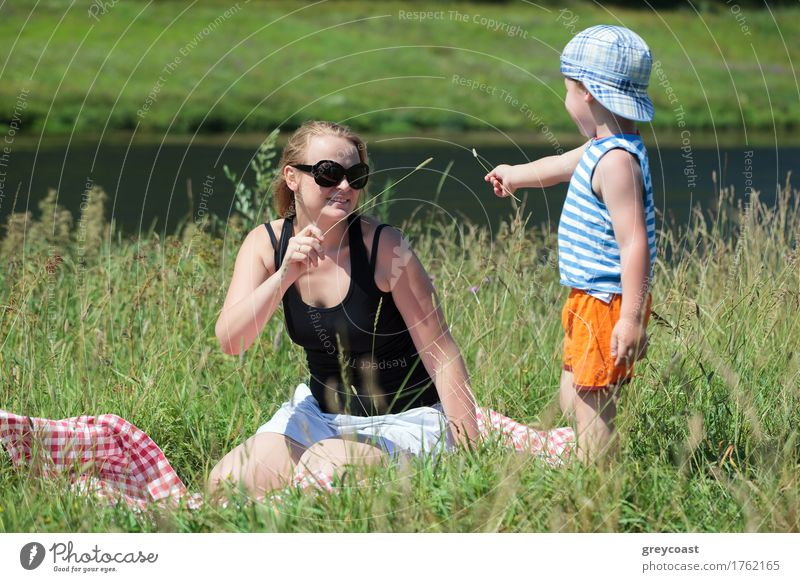 Happy mother and little son playing with grass on the meadow on the bank of a small river. Family fun outdoor Joy Relaxation Leisure and hobbies Playing Summer