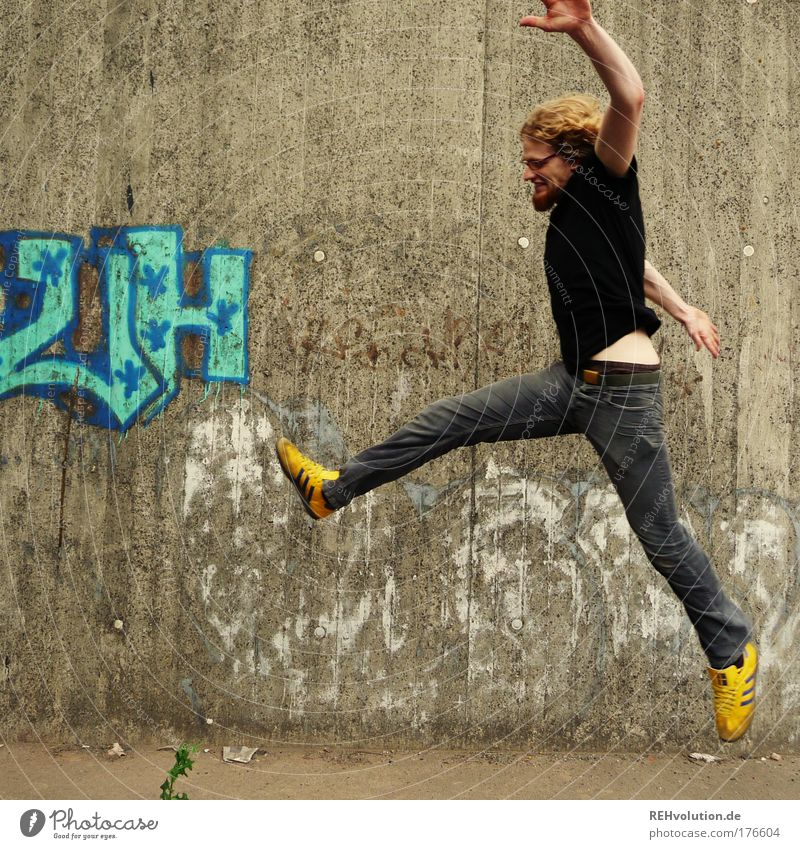 Young man jumps in front of a concrete wall Colour photo Exterior shot Copy Space left Neutral Background Day Full-length Profile Forward Style Joy Happy