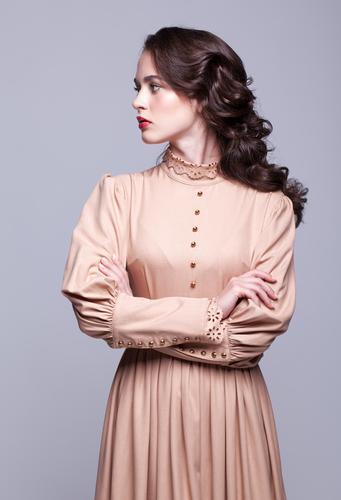 Portrait of young beautiful woman in retro beige dress Elegant Style Beautiful Skin Face Manicure Make-up Girl Woman Adults Hand Fashion Dress Brunette Thin
