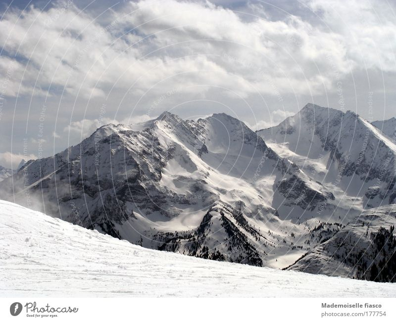 Ski slope and snowy mountain peaks Winter Snow Mountain Winter sports Clouds Alps Snowcapped peak Tall Above Blue Gray Black White Happy Idyll Subdued colour