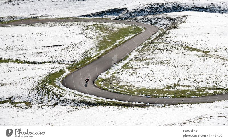 Cyclist goes downhill along a mountain road in a snowy landscape Beautiful Relaxation Vacation & Travel Tourism Trip Summer Winter Snow Mountain Sports Cycling
