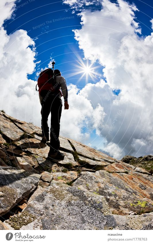 Man hiking up a rock hill against a dramatic cloudy sky Lifestyle Joy Vacation & Travel Tourism Adventure Expedition Summer Sun Mountain Sports Adults Nature