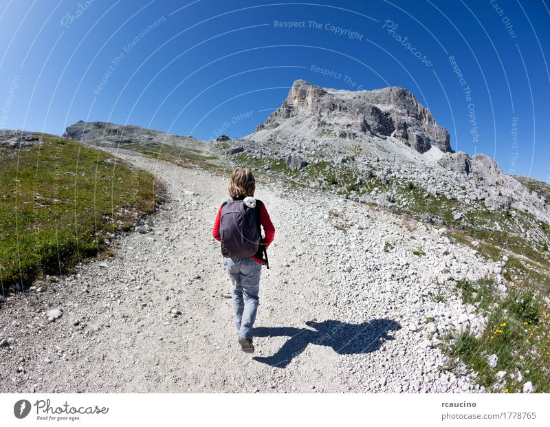 Young hiker walking on a mountain trail. Dolomities, Italy Child Sky Nature Vacation & Travel Man Blue Summer Landscape Loneliness Joy Mountain Adults