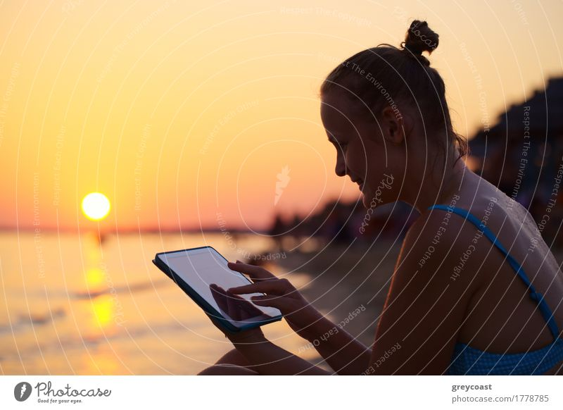 Smiling woman using pad on beach at sunset Happy Vacation & Travel Summer Sun Beach Ocean Computer Girl Young woman Youth (Young adults) 1 Human being