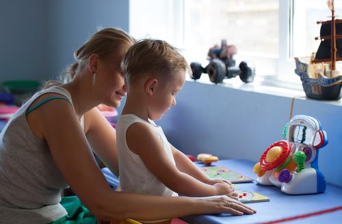 Mother watching little son playing learning game in his room Joy Playing Parenting Child Boy (child) Young woman Youth (Young adults) Adults Family & Relations